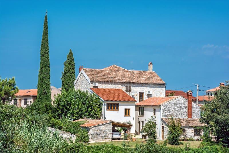 Entsteinte Häuser und Zypressenbäume, Ballen, Kroatien lizenzfreie stockfotos