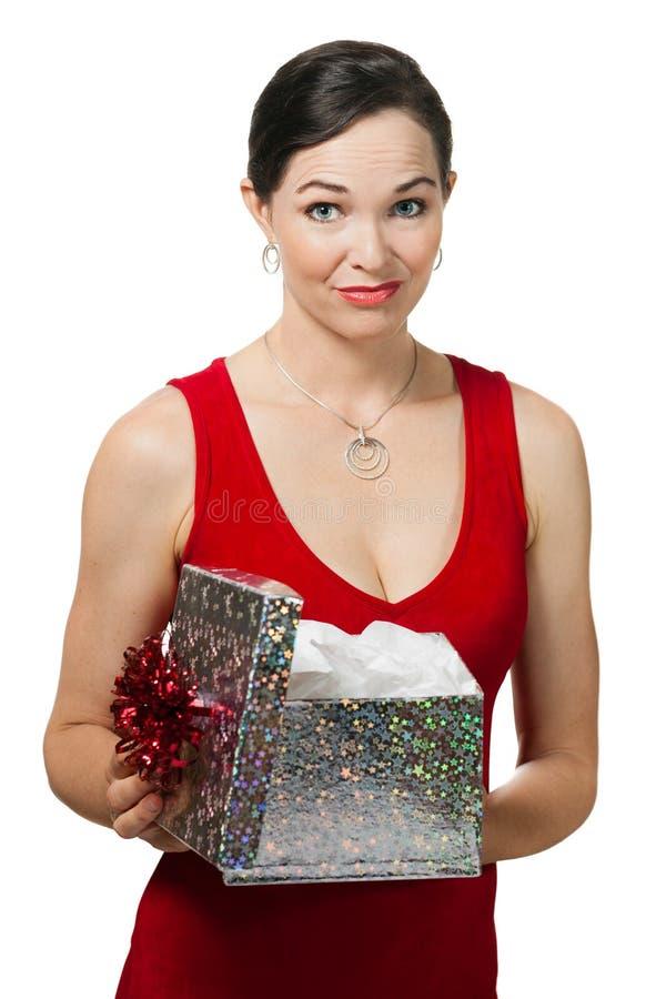 Enttäuschte Frau, die ein Geschenk hält lizenzfreie stockbilder
