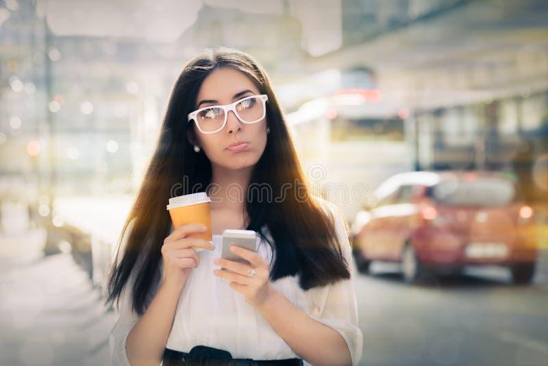 Enttäuschte junge Frau, die Smartphone und Kaffeetasse hält stockfoto