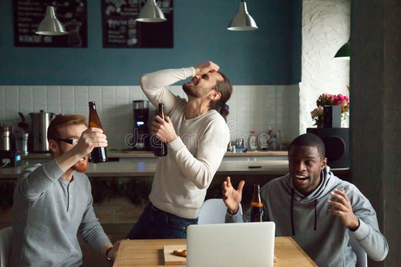 Enttäuschte verschiedene Männer entsetzt durch verlierendes aufpassendes Spiel auf lapt stockfotografie