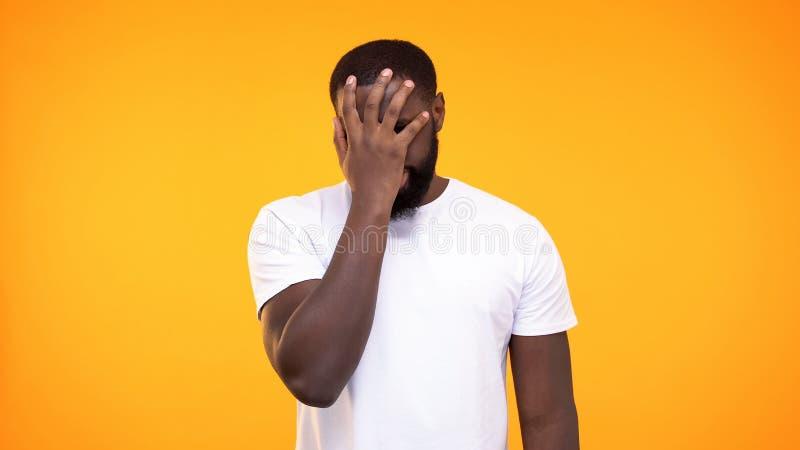 Enttäuschter afroer-amerikanisch Mann, der Gesichtspalmengeste auf gelbem Hintergrund tut stockfotografie