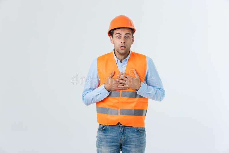 Enttäuschter hübscher Ingenieur, der orange Weste und Jeans mit dem Sturzhelm, lokalisiert auf weißem Hintergrund trägt stockfoto