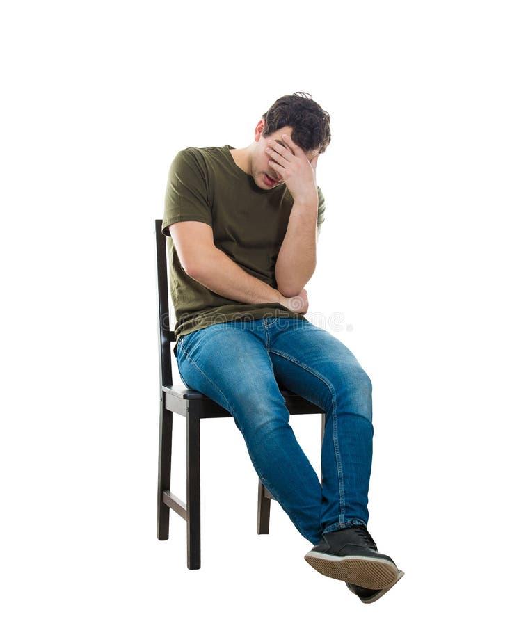 Enttäuschter Mann, der auf einem Stuhl sitzt stockfotos