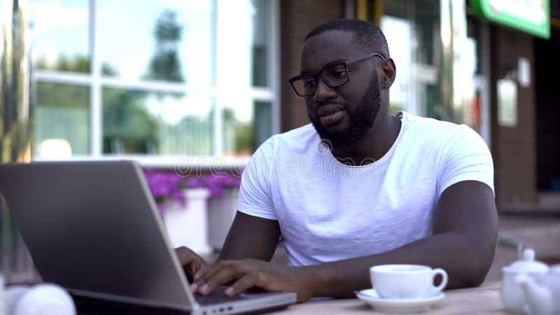 Enttäuschter Mann, der E-Mail auf Laptop-PC Café im im Freien, schlechte Nachrichten empfangend überprüft lizenzfreie stockfotografie