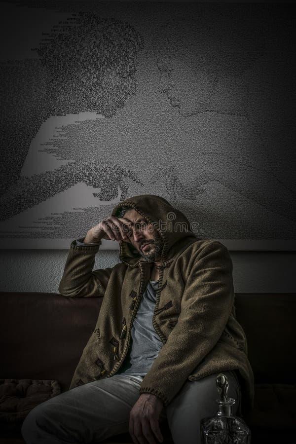 Enttäuschter Mann mit einer Haube und leeren gravierte Glasflasche Alkohol stockfoto