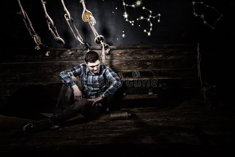 Enttäuschter Mann sitzt nahe einem Kasten und hält Glasflasche und Versuch lizenzfreies stockfoto