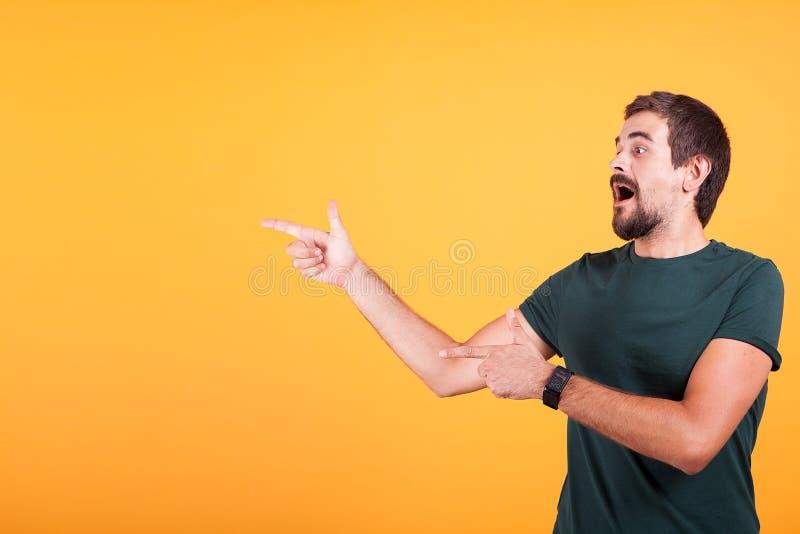 Entusiasm och uttrycksfull man som pekar på copyspacen royaltyfri fotografi