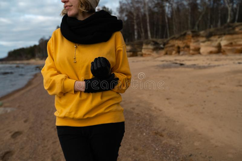 Entusiasta feliz del amante del deporte y de la moda que se resuelve en una playa que lleva el suéter amarillo brillante y guant foto de archivo