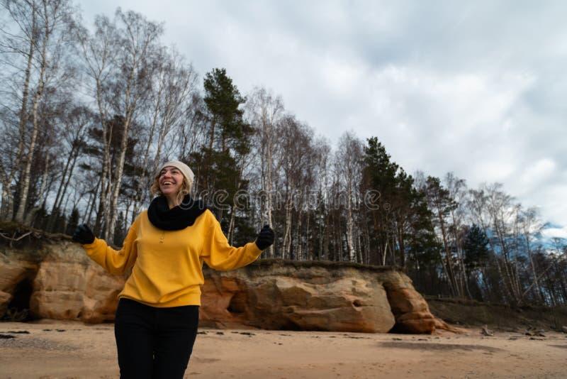 Entusiasta feliz del amante del deporte y de la moda que se resuelve en una playa que lleva el suéter amarillo brillante y guant imagen de archivo