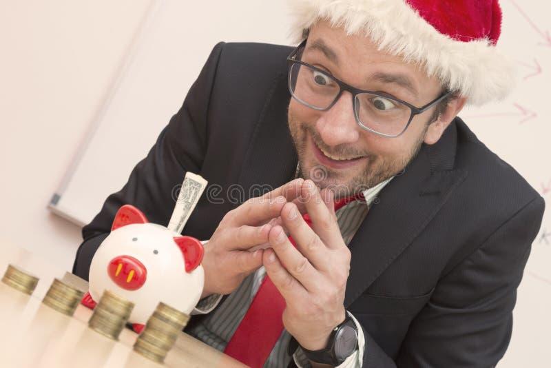 Entusiastisk affärsman med jultomtenhatten som ser piggybanken arkivfoto