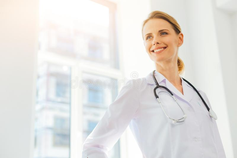 Entusiastisk kvinnlig doktor som ler, medan stå i sjukhus arkivfoto