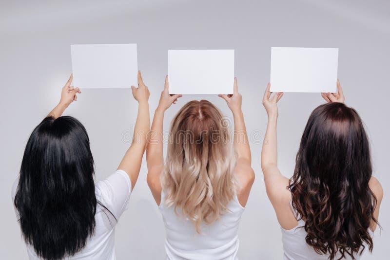 Entusiastiska kvinnliga aktivister som poserar med vitt tecken royaltyfri foto