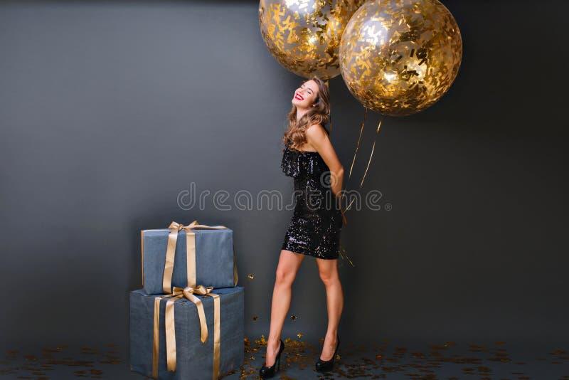Entuzjastyczna biała dziewczyna z błyskotanie helem szybko się zwiększać cieszący się urodzinowego photoshoot na ciemnym tle Uroc fotografia royalty free