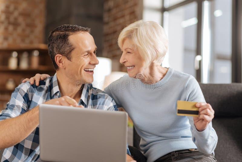 Entuzjastyczne starsze osoby matka i syn dyskutuje online zakupy obrazy royalty free