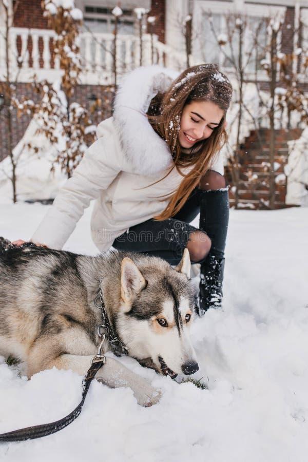 Entuzjastyczni europejscy dam spojrzenia z miłością przy jej psem, zmęczonym po gry w śniegu Ładna dziewczyna w eleganckim białym obrazy stock