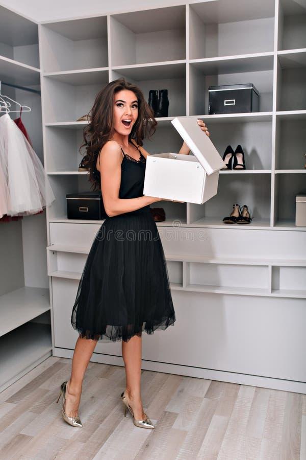 Entuzjastyczni młoda kobieta stojaki w eleganckiej garderobie z otwartym pudełkiem w jego ręki Ubierał w czerni sukni i zdjęcie stock