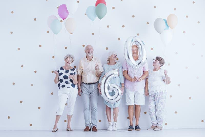 Entuzjastyczni starsi ludzi świętuje f z kolorowymi balonami obraz stock
