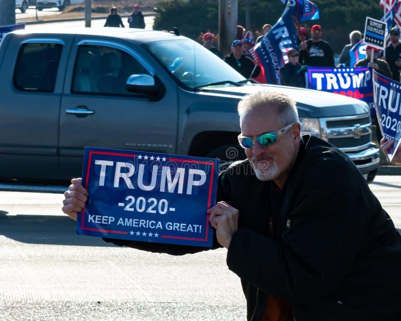 Entuzjastyczny człowiek i zwolennik Trumpa pokazuje swój znak do przejeżdżających pojazdów obraz royalty free