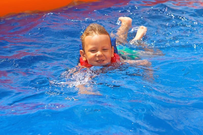 Entuzjastyczny dzieciak w kamizelce przy basenem zdjęcie stock