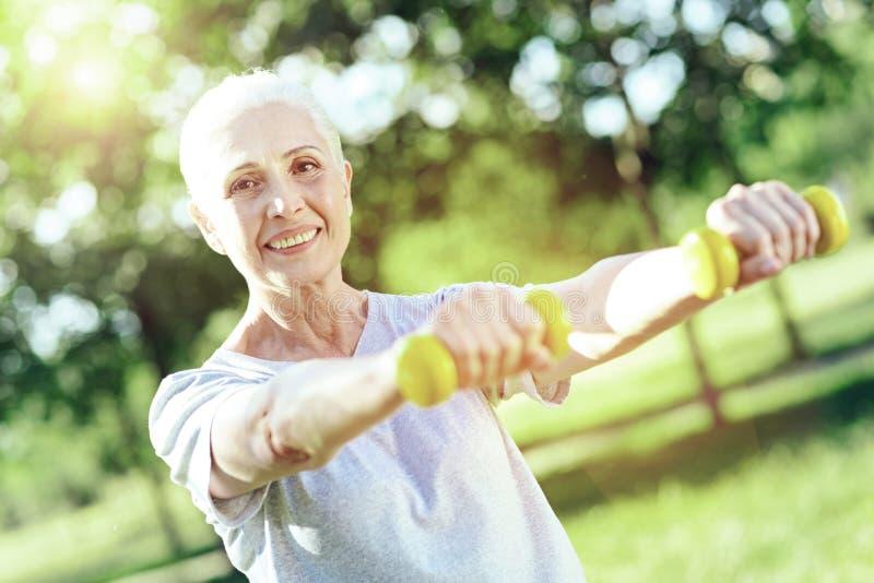 Entuzjastyczny emeryt satysfakcjonuje z małymi ręka ciężarami obrazy stock