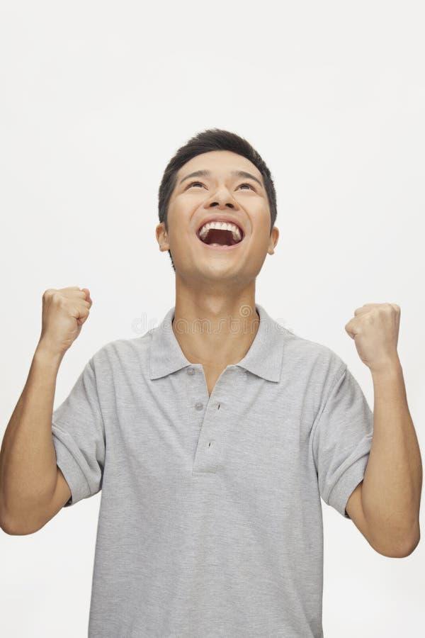 Entuzjastyczny młody człowiek z rękami podnosić i przyglądającym up, studio strzał zdjęcie royalty free