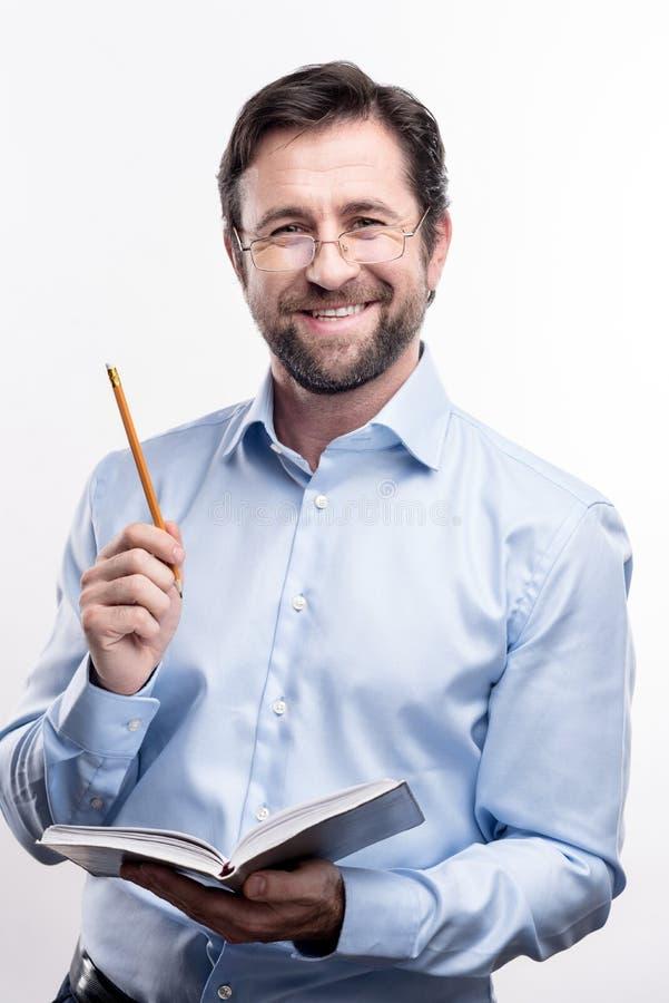 Entuzjastyczny profesor pozuje z notatnikiem i ołówkiem fotografia royalty free