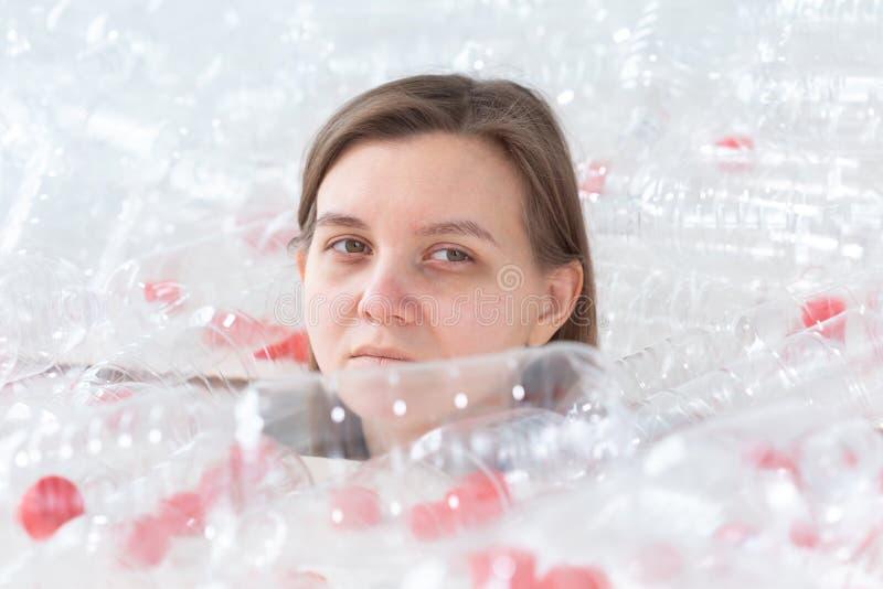 Entwässerte kranke Frau liegt in einem Stapel von Plastikflaschen Umweltverschmutzungsproblem Endnaturabfall stockfotos