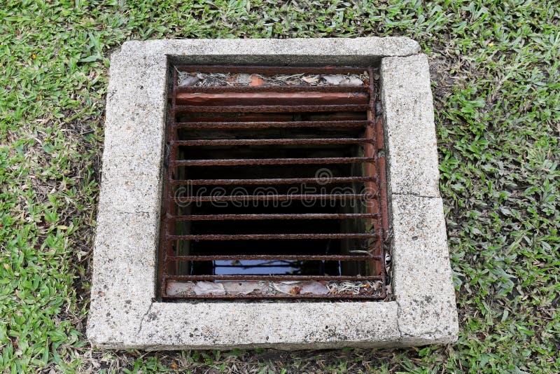 Entwässerungslochgitter für den Wasserschmutz alt, AbflussAbwasserrohrzement Schmutzwasserabfall auf dem Rasenboden, Entwässerung lizenzfreies stockbild