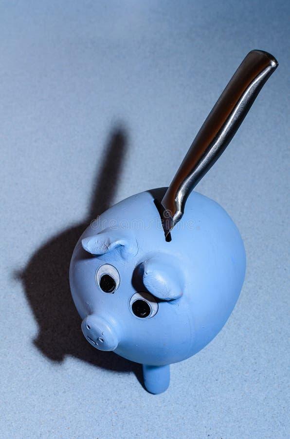 Entwenden von einem handgemachten Sparschwein über einem blauen silestone Schreibtisch stockbilder