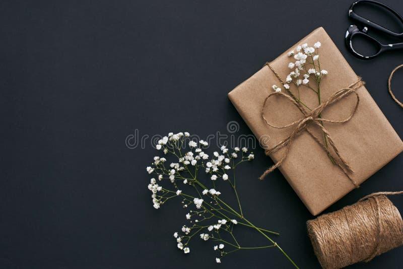 Entwerfen Sie Ihr Geschenk! Schöne Geschenkbox in braunem Papier Kraftpapiers auf dunklem Hintergrund stockfoto