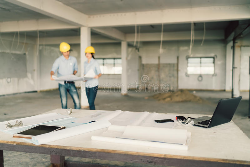 Entwerfen Sie, Laptop-Computer und industrielle Werkzeuge an der Baustelle mit zwei Ingenieuren oder Architekten, die im Hintergr stockbild