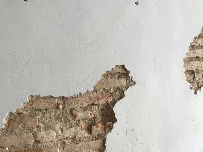 Entworfene antike Weißzementwand mit gebrochenem Raum, der alte Ziegelsteine zeigt stockfoto