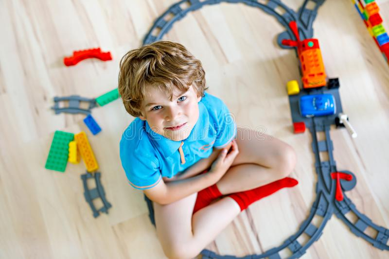 Entzückender kleiner blonder Kinderjunge, der mit bunten Plastikblöcken spielt und Bahnstation schafft Kind, das Spaß mit hat lizenzfreies stockfoto