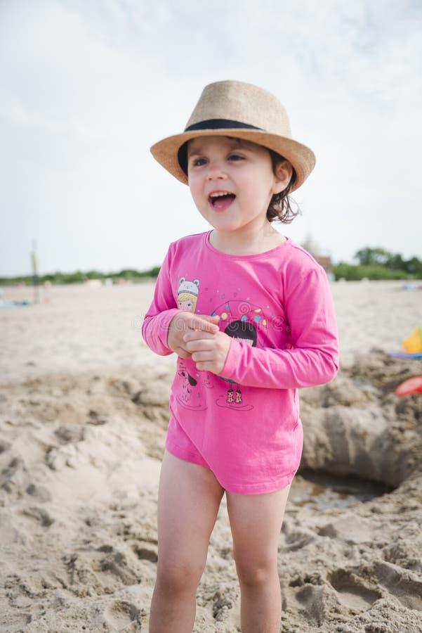 Entzückendes kleines Mädchen, das mit Sand auf dem Meer spielt lizenzfreie stockfotos