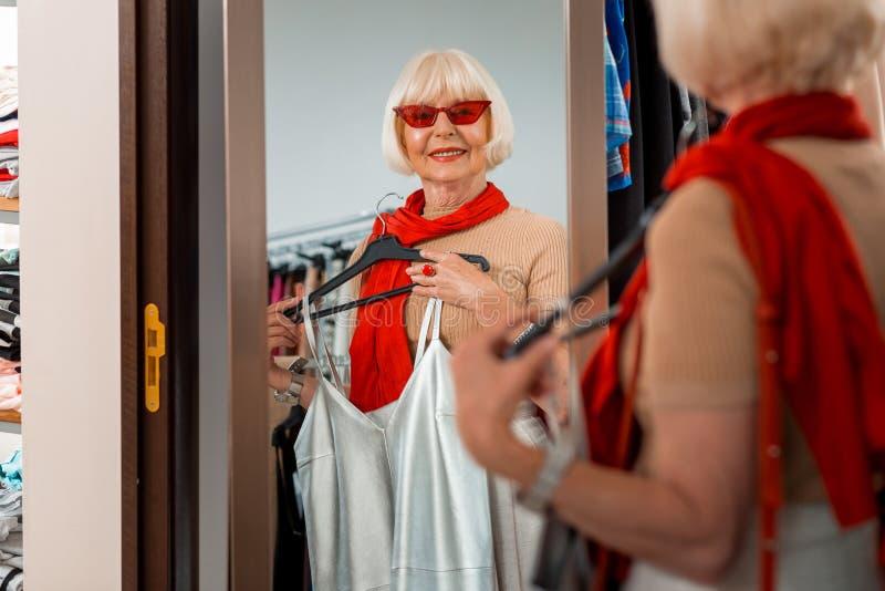 Entzückende ältere Frau, die im Einkaufsspiegel reflektiert wird stockfotografie