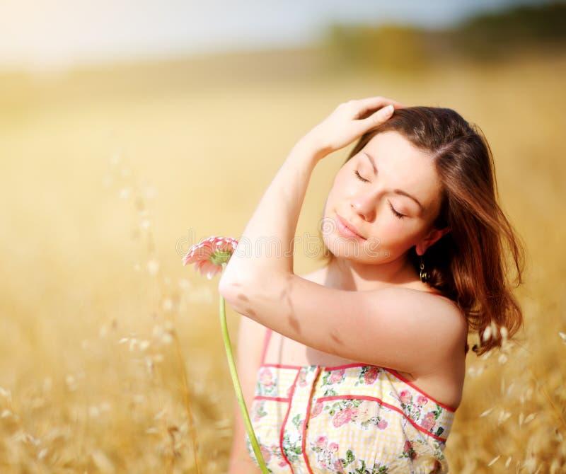 Entzückende Frau auf dem Gebiet mit Blume stockbilder