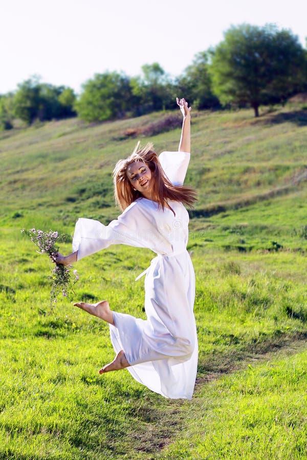 Entzückende Frau auf dem Gebiet mit Blumen lizenzfreie stockbilder