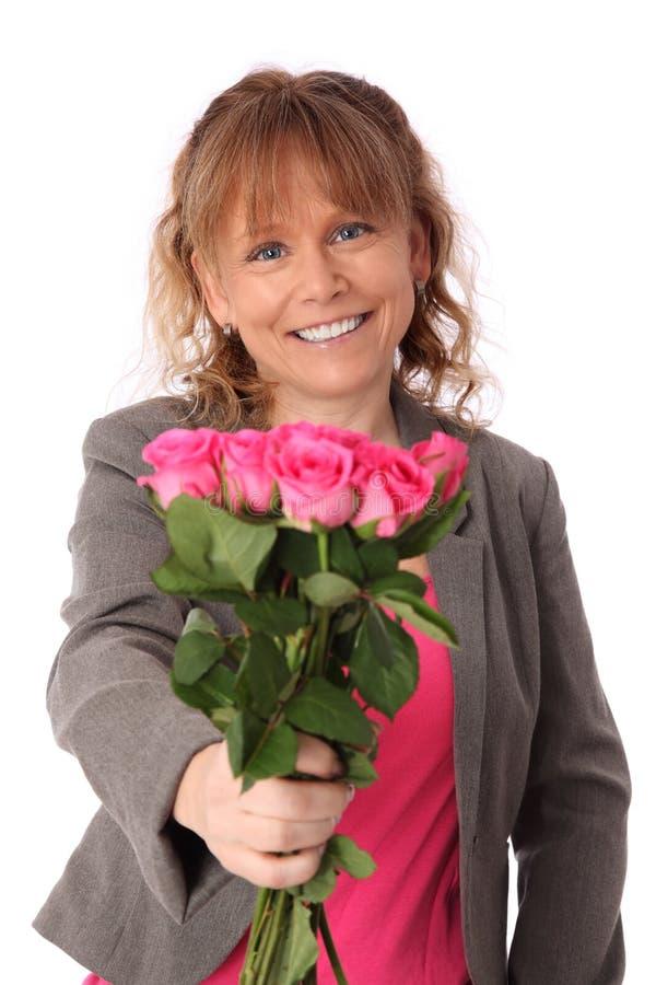 Entzückende Frau, die rosa Rosen mit einem Geschenk hält stockbilder