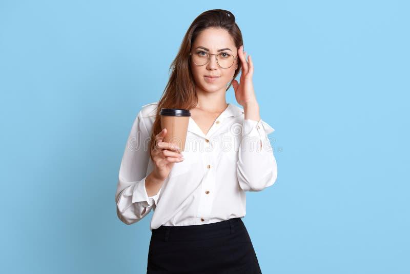 Entzückende Geschäftsfrau in der weißen Bluse und im schwarzen Rock mit Kaffee oder Tee in der Papierschale, hat Kopfschmerzen, h lizenzfreies stockfoto