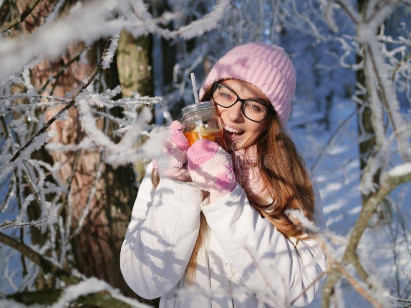 Entzückende glückliche junge Blondine im rosa Strickmützeschal, der Spaß heißen Tee vom Parkwald des Becherverschneiten winters t stockbilder