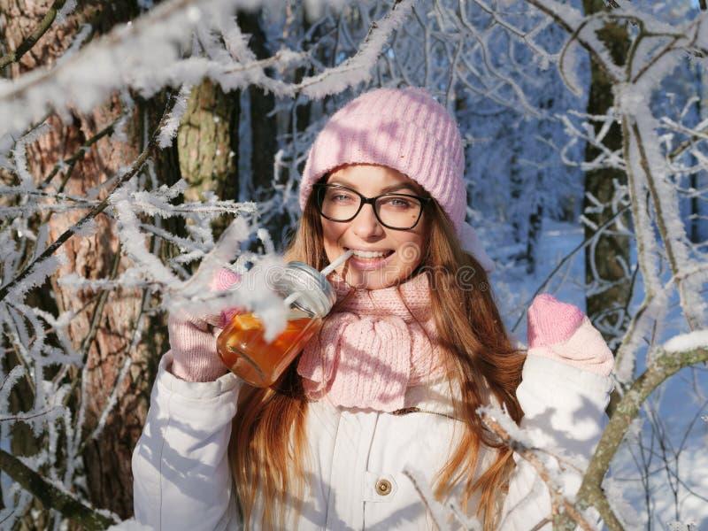 Entzückende glückliche junge Blondine im rosa Strickmützeschal, der Spaß heißen Tee vom Parkwald des Becherverschneiten winters t stockfotografie