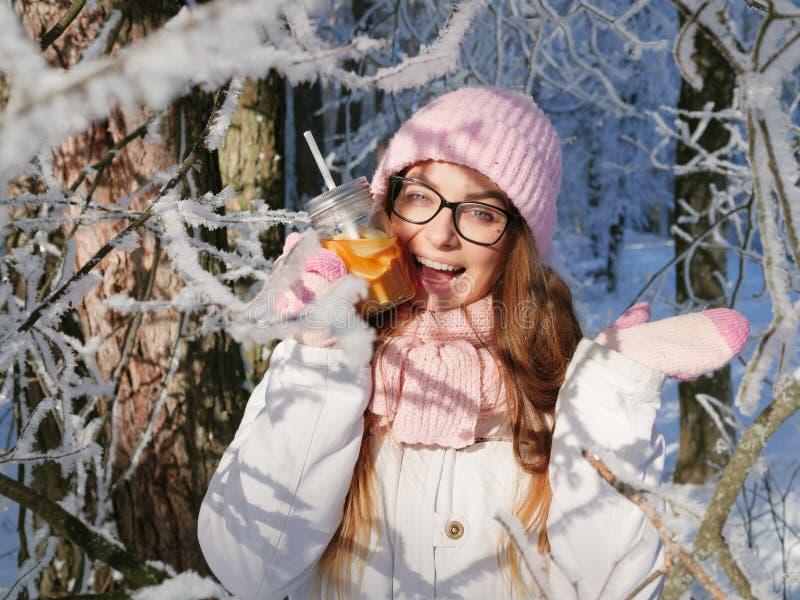 Entzückende glückliche junge Blondine im rosa Strickmützeschal, der Spaß heißen Tee vom Parkwald des Becherverschneiten winters t stockfoto