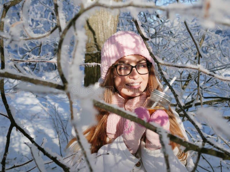 Entzückende glückliche junge Blondine im rosa Strickmützeschal, der Spaß heißen Tee vom Parkwald des Becherverschneiten winters t stockfotos