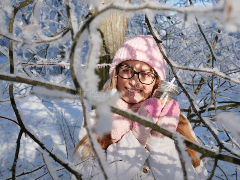 Entzückende glückliche junge Blondine im rosa Strickmützeschal, der Spaß heißen Tee vom Parkwald des Becherverschneiten winters t lizenzfreie stockbilder