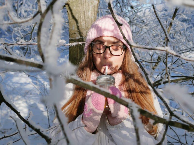 Entzückende glückliche junge Blondine im rosa Strickmützeschal, der Spaß heißen Tee vom Parkwald des Becherverschneiten winters t lizenzfreie stockfotografie