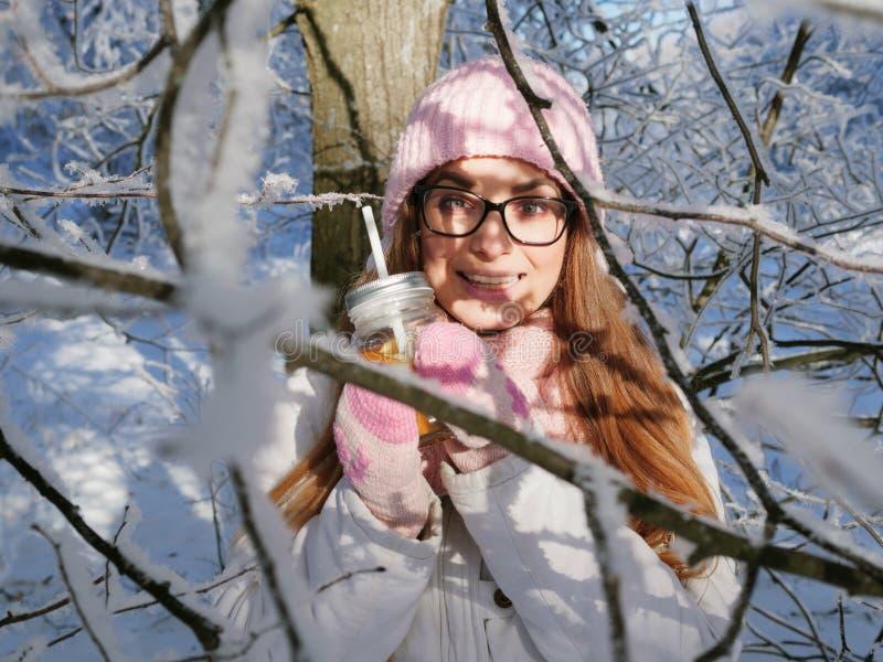 Entzückende glückliche junge Blondine im rosa Strickmützeschal, der Spaß heißen Tee vom Parkwald des Becherverschneiten winters t lizenzfreie stockfotos