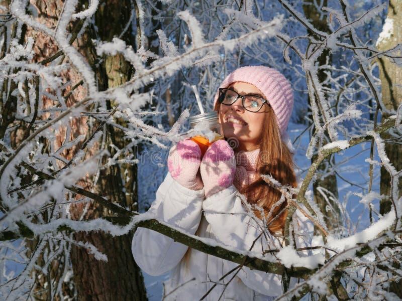 Entzückende glückliche junge Blondine im rosa Strickmützeschal, der Spaß heißen Tee vom Parkwald des Becherverschneiten winters t lizenzfreies stockbild