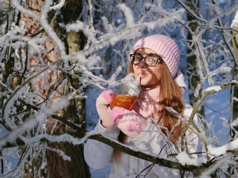 Entzückende glückliche junge Blondine im rosa Strickmützeschal, der Spaß heißen Tee vom Parkwald des Becherverschneiten winters t lizenzfreies stockfoto