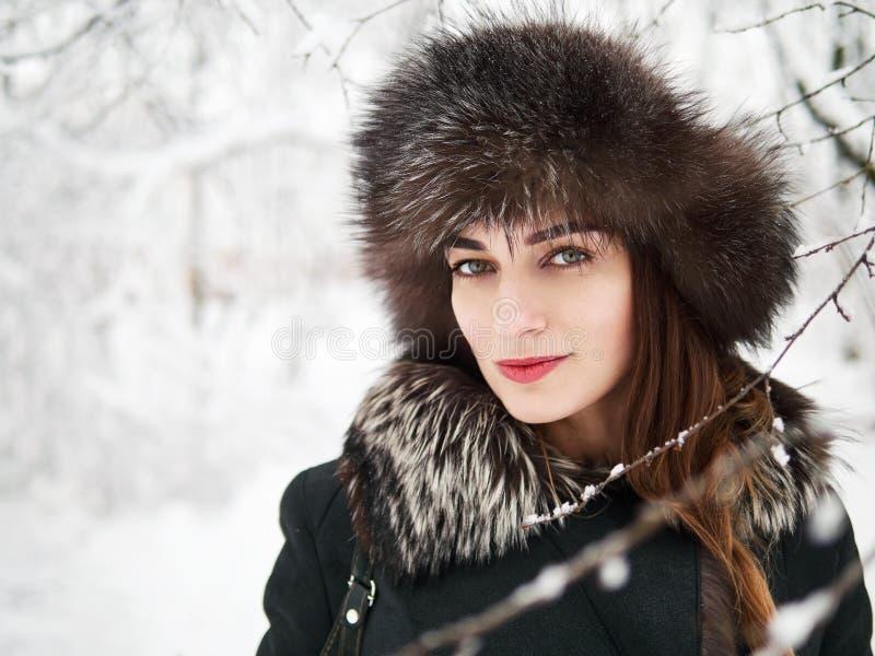 Entzückende glückliche junge Brunettefrau im Pelzhut, der Parkwald des Spaßverschneiten winters in der Natur hat lizenzfreie stockfotos