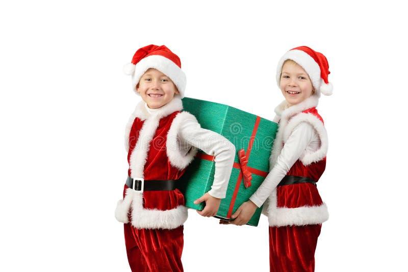 Entzückende glückliche Jungen in Sankt kleidet das Halten der Weihnachtsgeschenkbox Lokalisierter weißer Hintergrund stockfoto